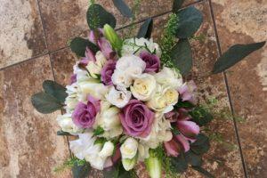 Lavender roses, white spray roses, white lisianthus, white tulips, lavender alstroemeria, white hydrangea, pennycress and silver dollar eucalyptus.